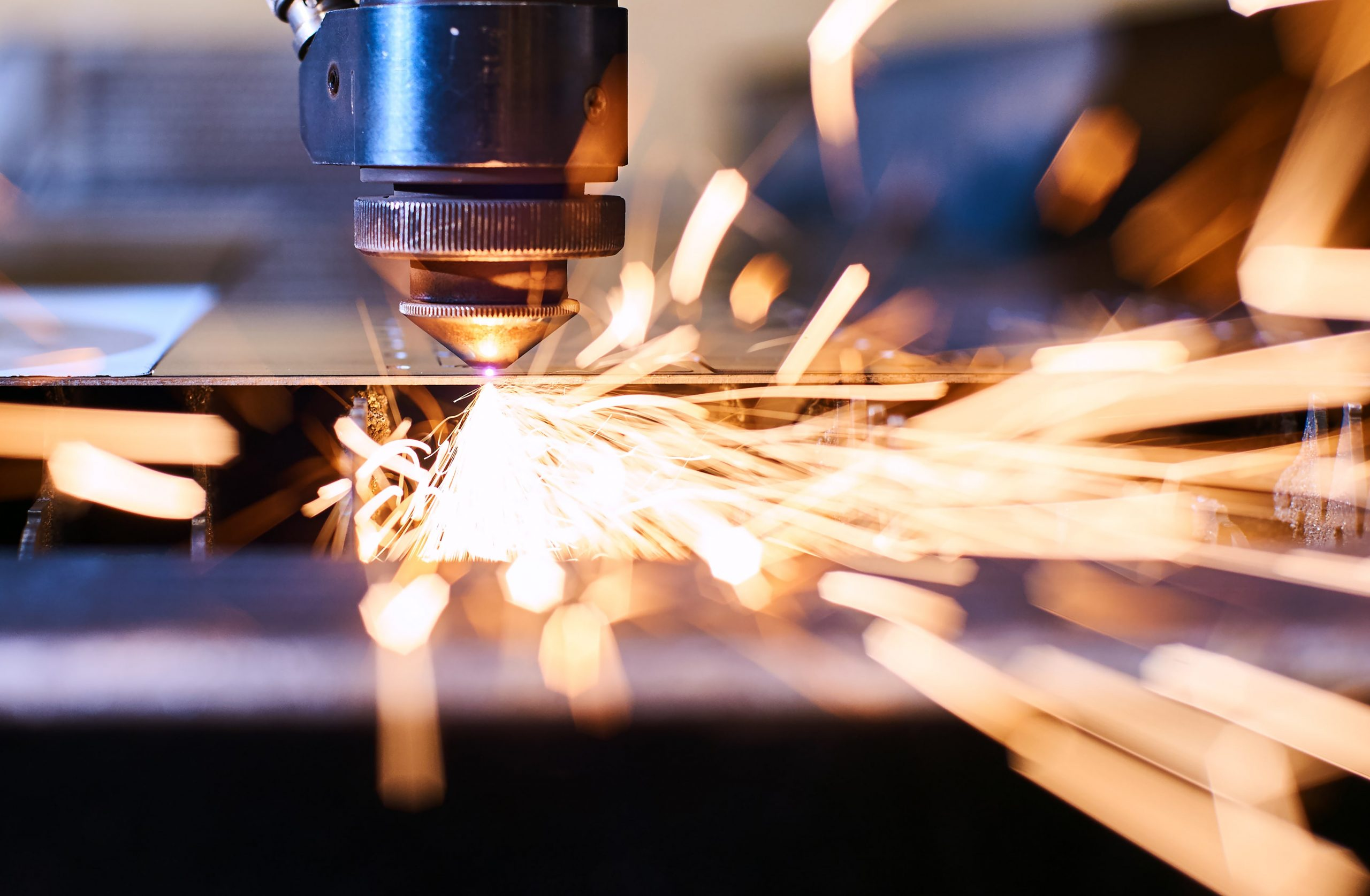CNC Laser cutting of metal with sparks at Tri-Mac Manufacturing